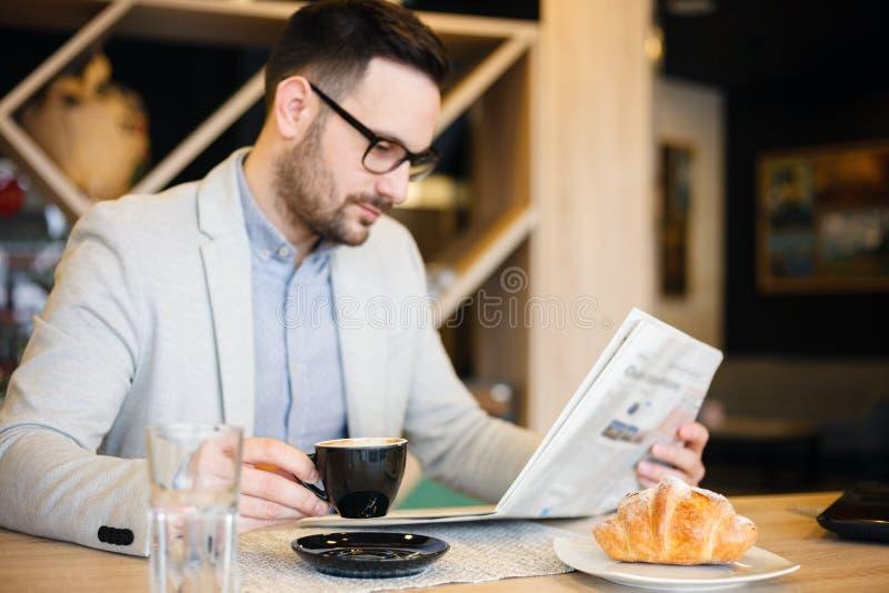 De jonge kranten van de architectenlezing en het drinken koffie in een moderne koffie Het concept van het werk overal stock foto's