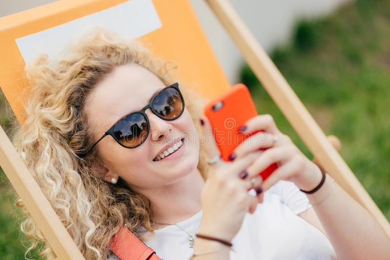 De jonge krullende blondevrouw ligt in hangmat, geniet de zomer van dag, bloggs en de praatjes via slimme telefoon, draagt in sch stock afbeelding