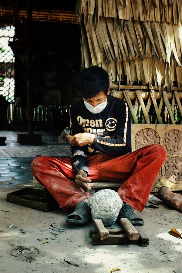 de jonge kunstenaarsbeeldhouwer snijdt een hoofd gestalte gegeven steenblok op zijn workshop met traditionele technieken royalty-vrije stock fotografie