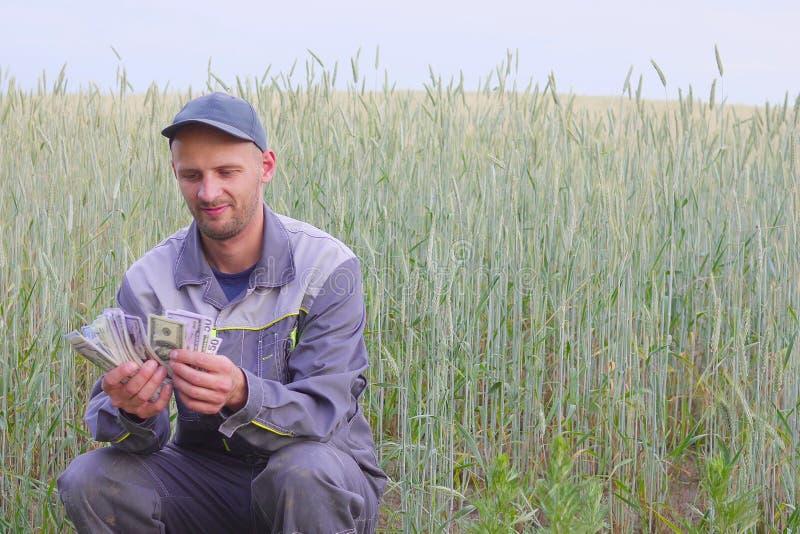 De jonge landbouwer heeft heel wat geld Het concept succes van zaken in landbouw stock fotografie