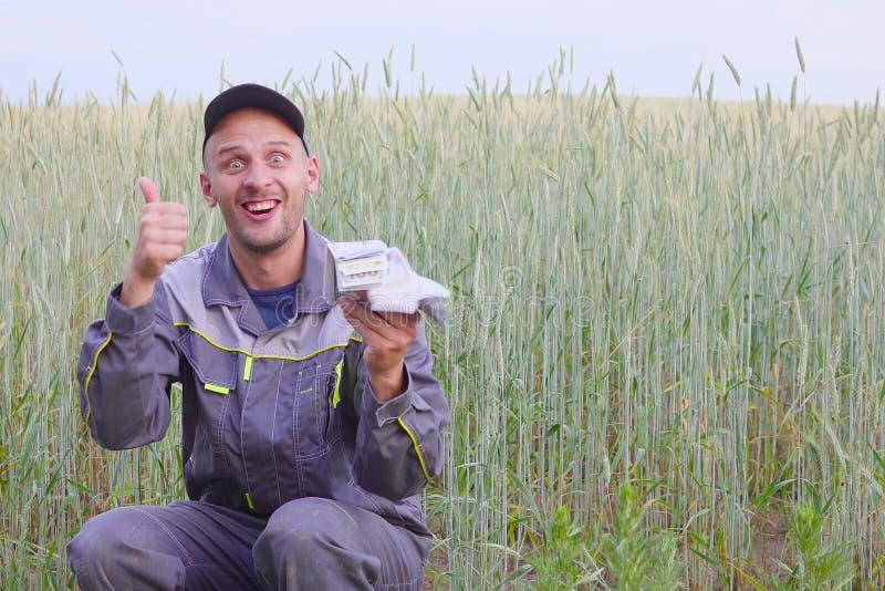 De jonge landbouwer heeft heel wat geld Het concept succes van zaken in landbouw royalty-vrije stock afbeeldingen