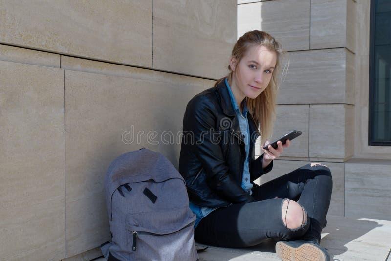 De jonge langharige reiziger van de vrouwenstudente in zwarte jeans en een zitting van het leerjasje met de benen over elkaar met royalty-vrije stock afbeelding
