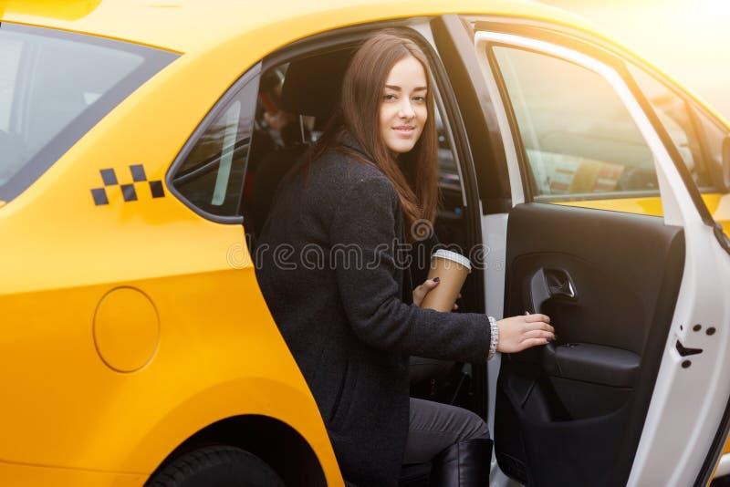 De jonge leuke donkerbruine koffie van de vrouwenholding in achterbank van taxi royalty-vrije stock afbeelding