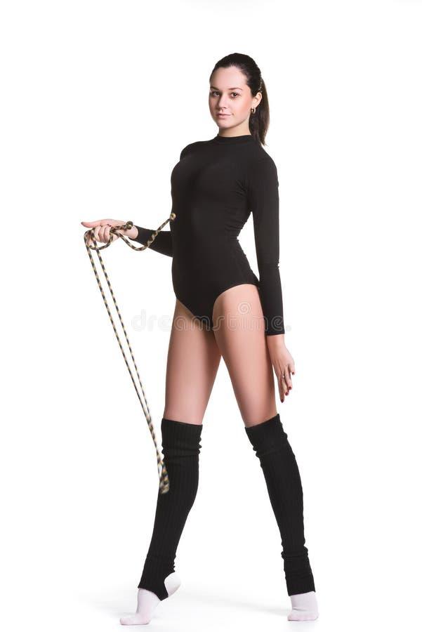 De jonge leuke vrouw in turnerkostuum toont atletische vaardigheid met gymnastiek- kabel op witte achtergrond royalty-vrije stock foto