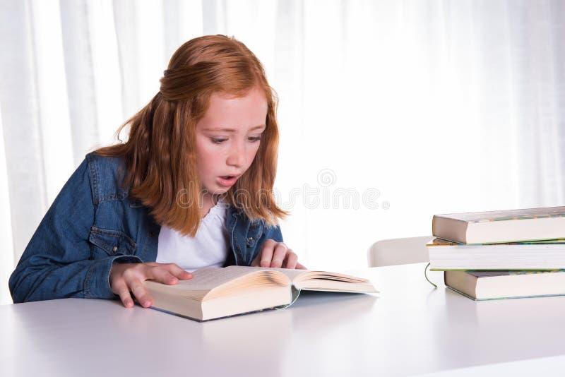 De jonge lezing van het roodharigemeisje in boeken - zij is doen schrikken royalty-vrije stock fotografie