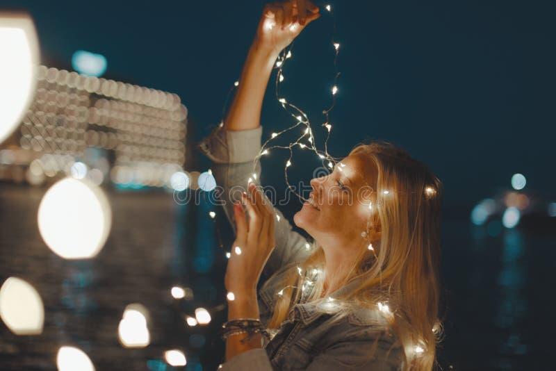 De jonge lichten van de de slingerfee van de blondevrouw bij nacht royalty-vrije stock afbeelding