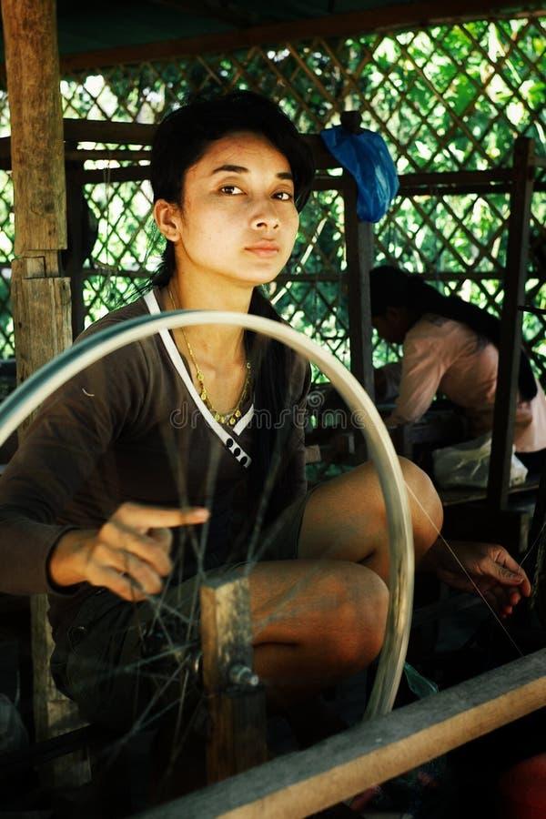 de jonge lokale damehand die een spoel van garen met een huis spinnen maakte spinnewiel van een fietswiel omgezet stock fotografie