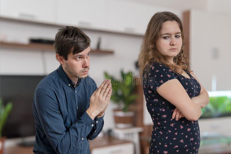 De jonge man bedelt thuis voor vergiffenis jonge boze vrouw stock afbeeldingen