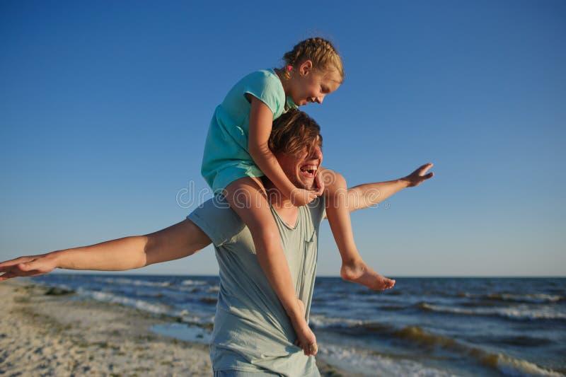 De jonge man brengt gaily tijd met de kleine dochter aan het zandige strand door stock fotografie