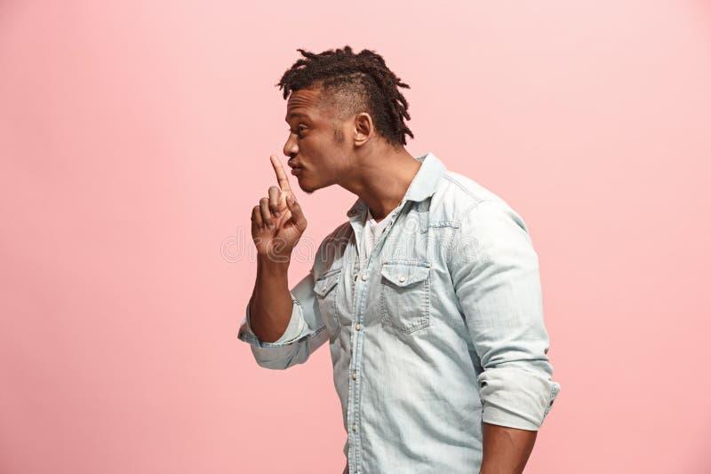 De jonge man die een geheim achter haar fluisteren overhandigt roze achtergrond stock fotografie