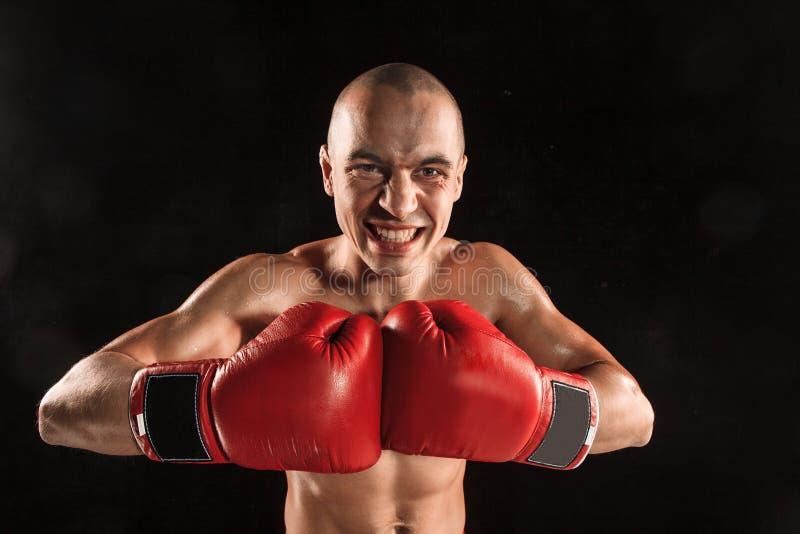De jonge man die op zwarte met het gillen gezicht kickboxing stock foto's