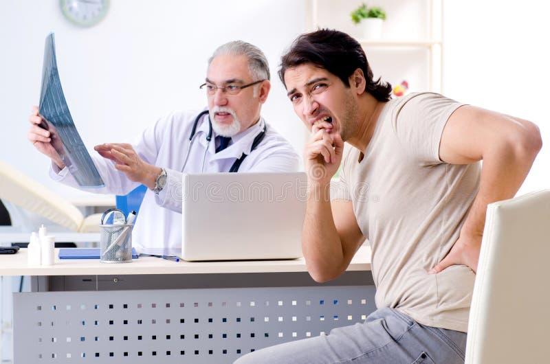 De jonge man die oude mannelijke artsenradioloog bezoeken royalty-vrije stock afbeeldingen