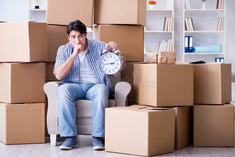 De jonge man die zich binnen aan nieuw huis met dozen bewegen stock afbeelding