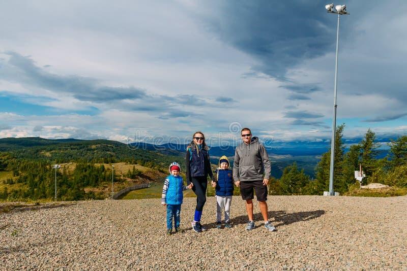 De jonge man en de vrouw en twee kinderen bevinden zich op de berg tegen de blauwe bewolkte hemel royalty-vrije stock foto