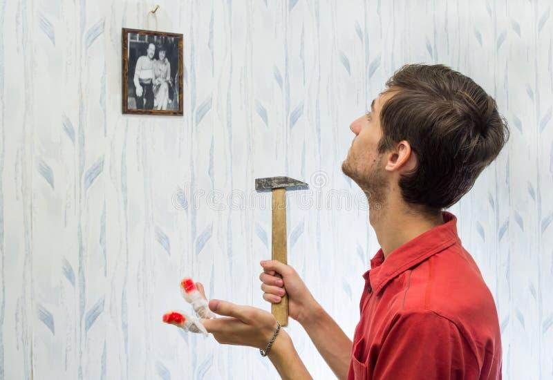 De jonge man hing beelden op de muur, die binnenland verbeteren