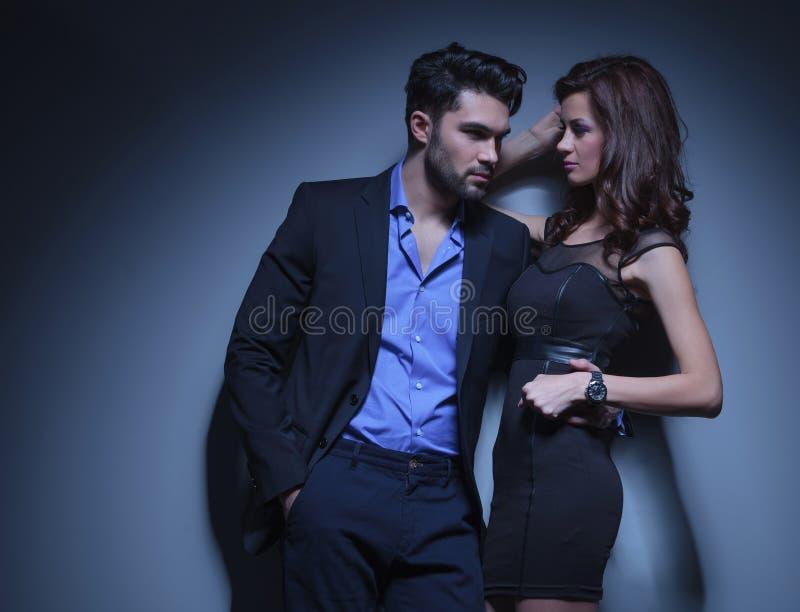 De jonge man houdt een vrouw en kijkt weg royalty-vrije stock afbeelding