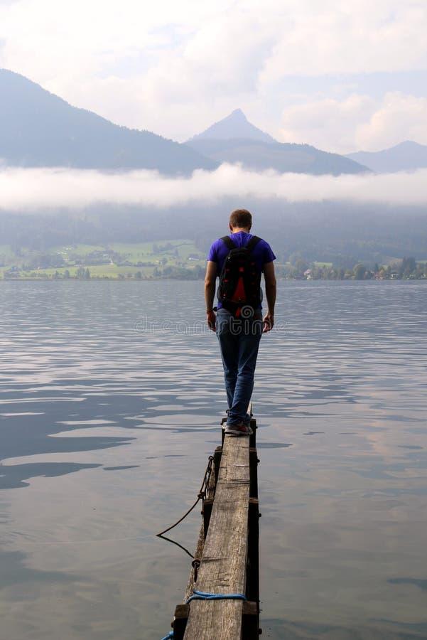 De jonge man loopt op een brug met de mening over het meer dichtbij aan bergen in het bewolkte weer royalty-vrije stock fotografie