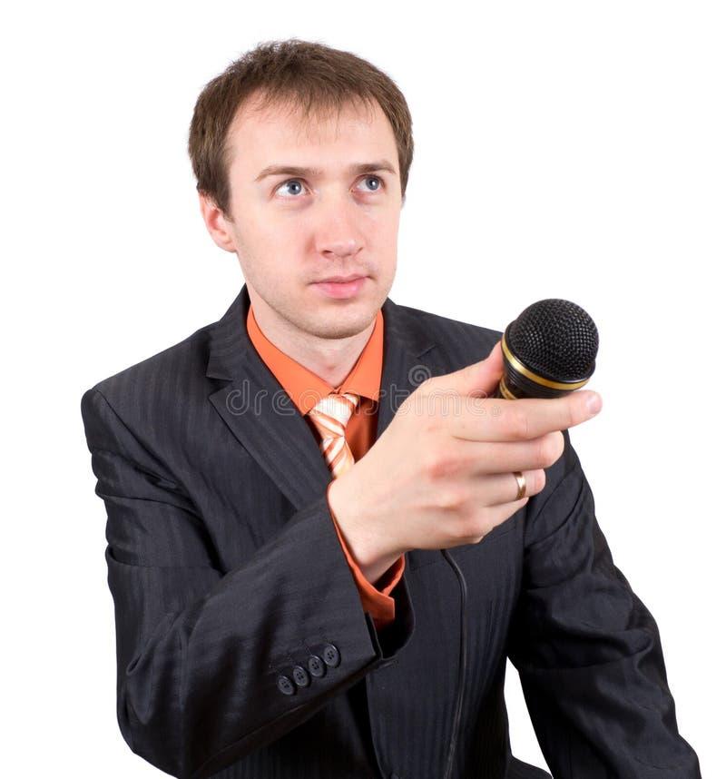 De jonge man met een microfoon interviewt stock afbeelding