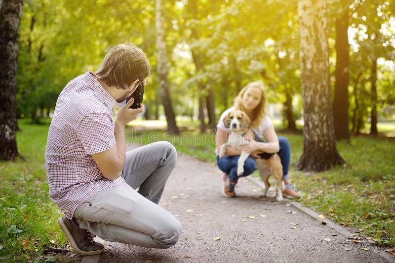De jonge man neemt een geschotene mooie vrouw met hond in zonnig de zomerpark Datum of het lopen stock afbeelding