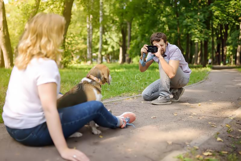 De jonge man neemt een geschotene mooie vrouw met hond in zonnig de zomerpark Datum of het lopen royalty-vrije stock afbeeldingen