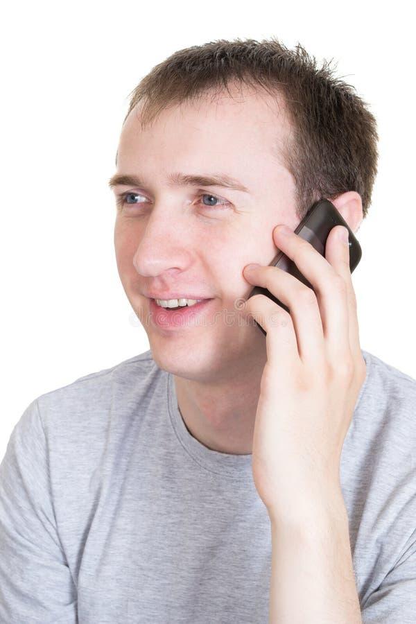 De jonge man spreekt door een mobiele geïsoleerde telefoon, royalty-vrije stock afbeelding