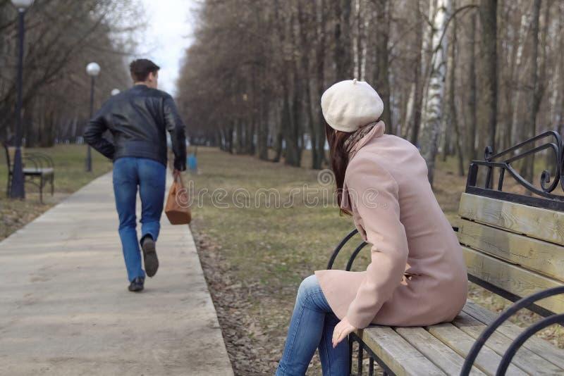 De jonge man steelt een vrouwen` s zak van een bank in het park royalty-vrije stock afbeeldingen