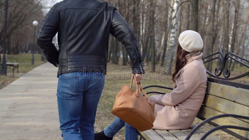 De jonge man steelt een vrouwen` s zak van een bank in het park royalty-vrije stock foto