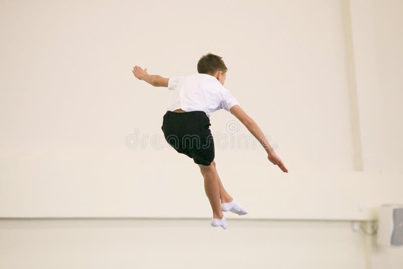 De jonge man voert gymnastiek- oefeningen in de gymnastiek uit stock afbeelding