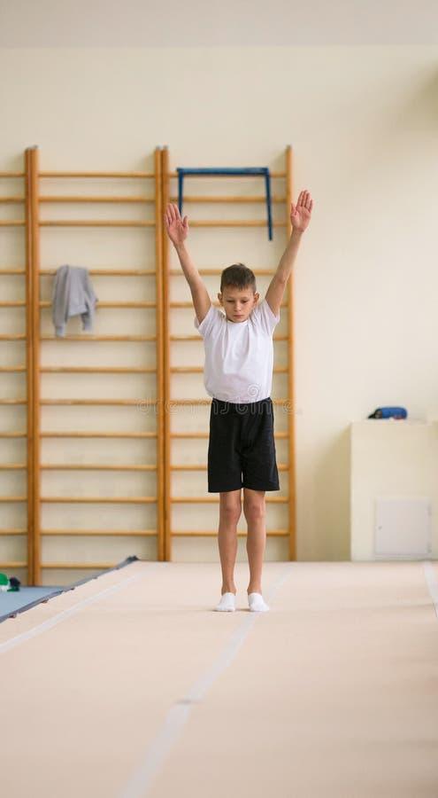 De jonge man voert gymnastiek- oefeningen in de gymnastiek uit royalty-vrije stock foto's