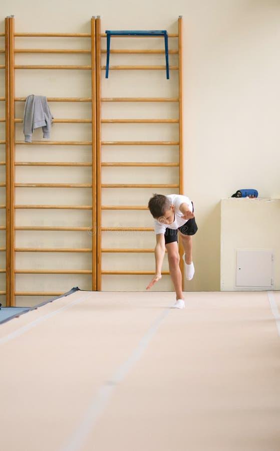 De jonge man voert gymnastiek- oefeningen in de gymnastiek uit royalty-vrije stock afbeelding