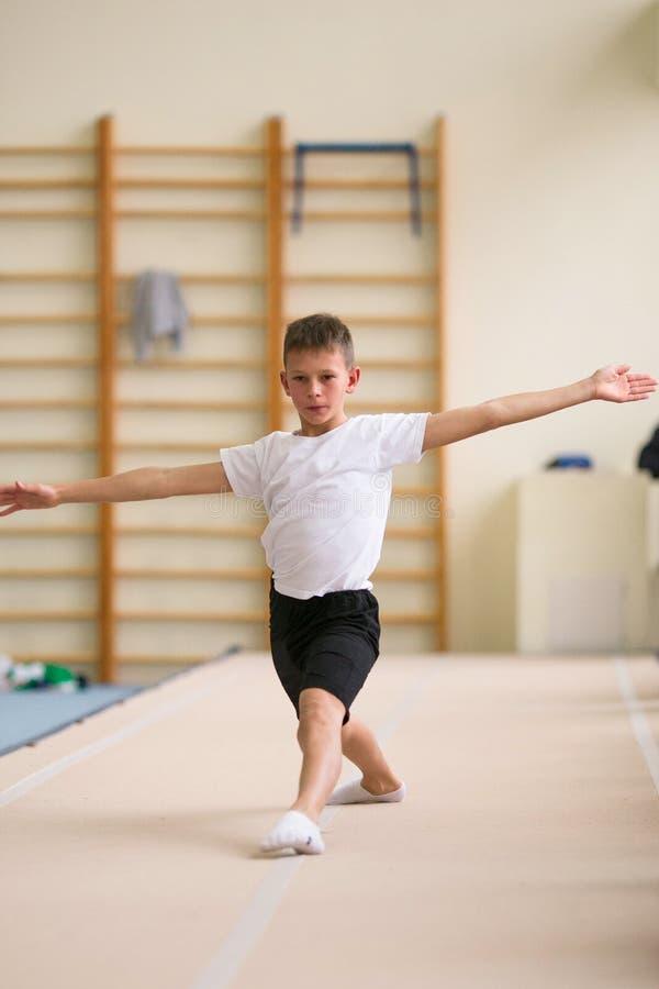 De jonge man voert gymnastiek- oefeningen in de gymnastiek uit royalty-vrije stock fotografie