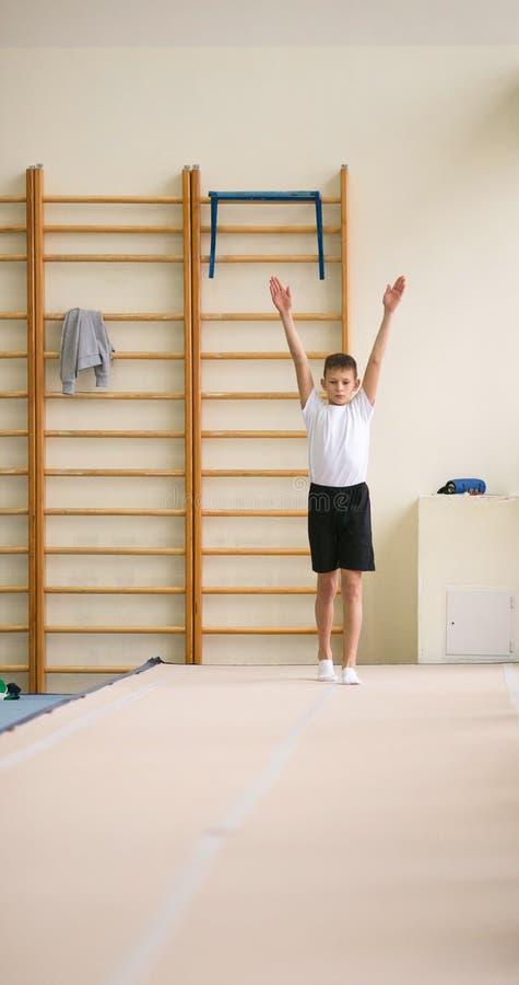 De jonge man voert gymnastiek- oefeningen in de gymnastiek uit stock afbeeldingen