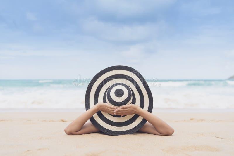 De jonge maniervrouw ontspant op het strand Gelukkige eilandlevensstijl Wit zand, blauwe bewolkte hemel en kristaloverzees van tr royalty-vrije stock afbeeldingen