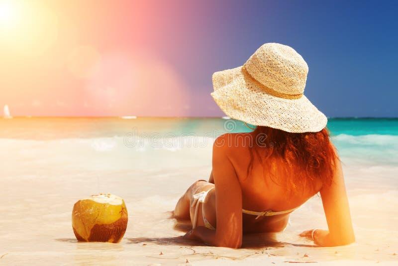 De jonge maniervrouw ontspant op het strand Gelukkige eilandlevensstijl Wit zand, blauwe bewolkte hemel en kristaloverzees van tr royalty-vrije stock foto