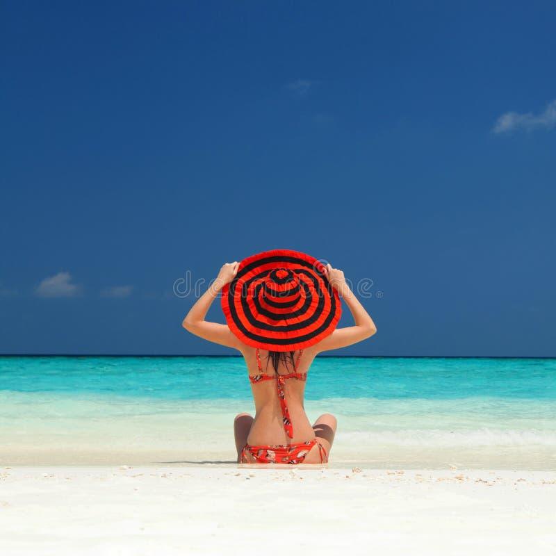 De jonge maniervrouw ontspant op het strand Gelukkige Levensstijl Wit zand, blauwe hemel en kristaloverzees van tropisch strand royalty-vrije stock fotografie