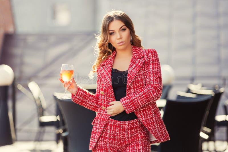 De jonge maniervrouw in rood tweedjasje en de borrels passen bij stoepkoffie aan royalty-vrije stock fotografie