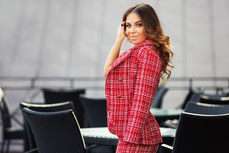 De jonge maniervrouw in rood tweedjasje en de rok passen bij stoepkoffie aan royalty-vrije stock fotografie