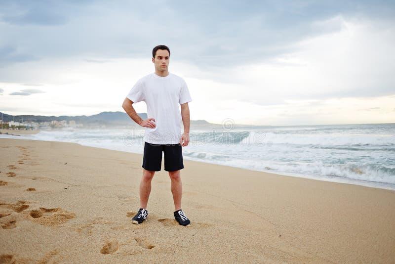 De jonge mannelijke agent kleedde zich in de witte t-shirt die zich op het zand bevinden die nadat de intensieve ochtend aanstoot stock afbeelding