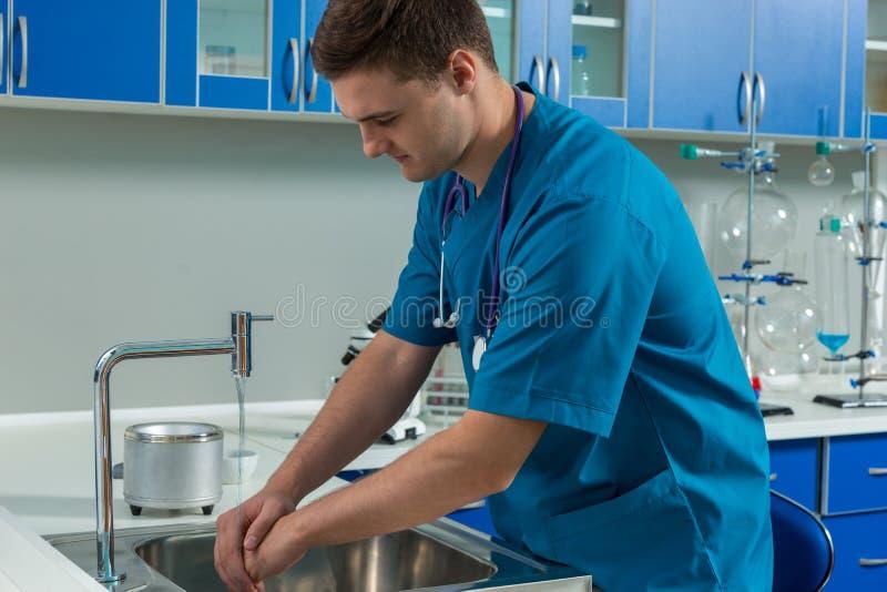 De jonge mannelijke arts in eenvormige was van hem dient het moderne laboratorium in stock foto's
