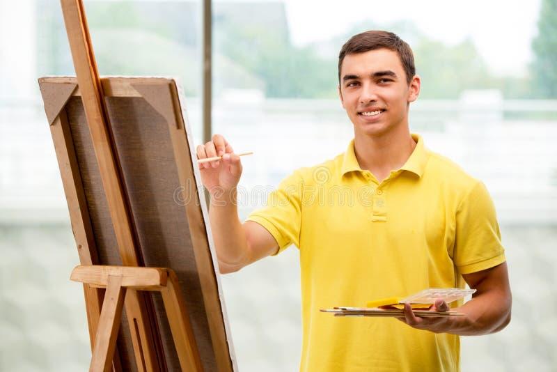 De jonge mannelijke beelden van de kunstenaarstekening in heldere studio stock foto