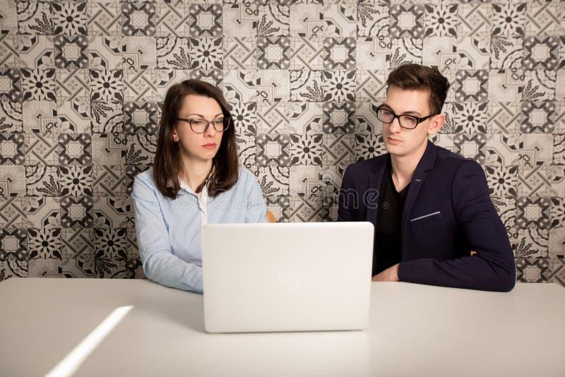 De jonge mannelijke en vrouwelijke partners die achter een computer zitten controleren en het denken aan iets stock afbeelding