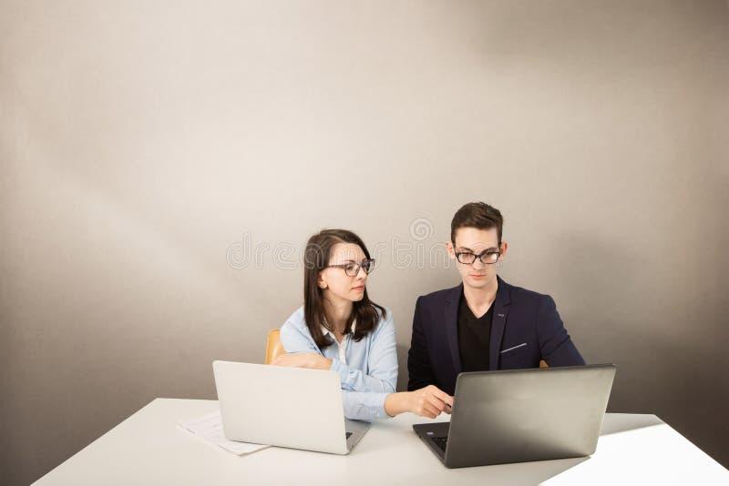 De jonge mannelijke en vrouwelijke partners die achter een computer zitten controleren en het denken aan iets stock foto