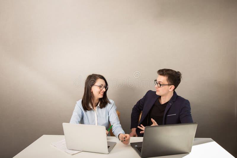 De jonge mannelijke en vrouwelijke partners die achter een computer zitten controleren en het denken aan iets royalty-vrije stock foto's