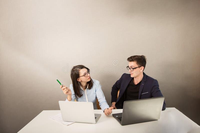 De jonge mannelijke en vrouwelijke partners die achter een computer zitten controleren en het denken aan iets stock fotografie