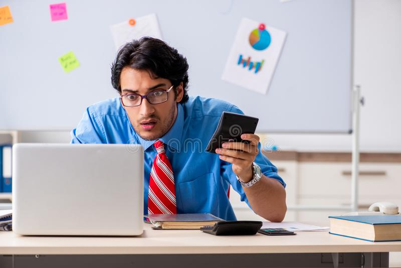 De jonge mannelijke financiële manager die in het bureau werken royalty-vrije stock afbeeldingen