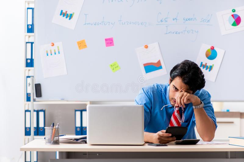 De jonge mannelijke financiële manager die in het bureau werken royalty-vrije stock afbeelding