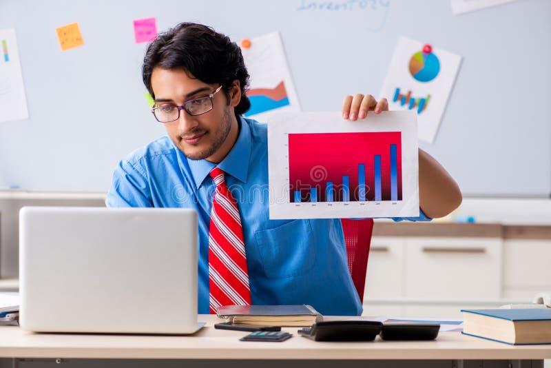 De jonge mannelijke financiële manager die in het bureau werken stock afbeeldingen