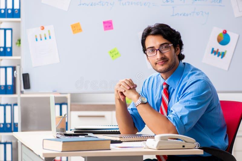 De jonge mannelijke financi?le manager die in het bureau werken royalty-vrije stock afbeeldingen