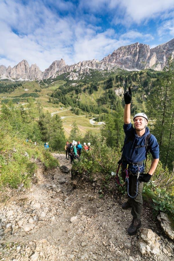 De jonge mannelijke klimmer bekijkt omhoog a via Ferrata in het Dolomiet en vele mensen bevinden zich achter hem stock foto