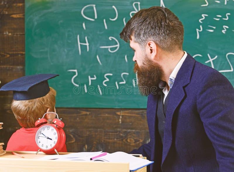De jonge mannelijke leraar begeleidt zijn kindstudent aan het leren terwijl de zoon bord met gekrabbel bekijkt, aanwezig zijnd royalty-vrije stock afbeeldingen